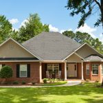 Colonial brick house with beautifully landscaped front yard and mature oak trees